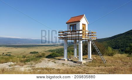 Completely renovated fire observation tower with wooden fence and metal ladders put on high observation point over large open area