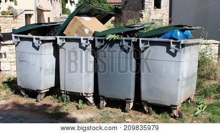 Completely full four gray plastic trash containers with green lids waiting for pickup