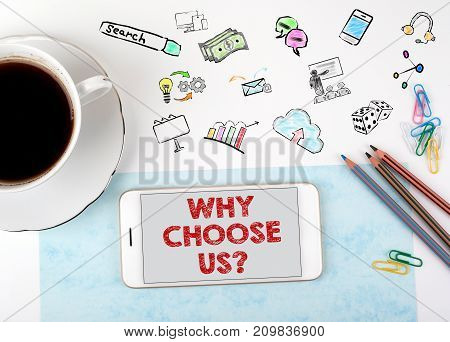 Why Choose Us. Mobile phone and coffee cup on a white office desk.