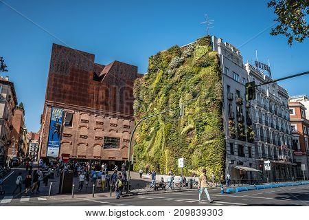 Madrid, Spain - October 14, 2017: Outdoors view of CaixaForum Madrid is a museum and cultural center in Paseo del Prado sponsored by La Caixa Bank. On the house next to it, there is a green wall