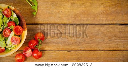 Overhead view of fresh salad in bowl by tomatoes on wooden table