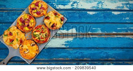 Overhead view of pizzas arranged on wooden table