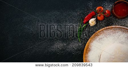 Overhead view of pizza dough with flour and ingredients on table