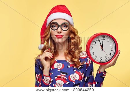 Christmas New Year. Young Woman in Santa Claus hat with Red Clock. Happy Smiling Redhead Girl in Stylish fashion Xmas Holiday Festive Dress. Portrait Pretty Model on Yellow. Christmas Colorful concept