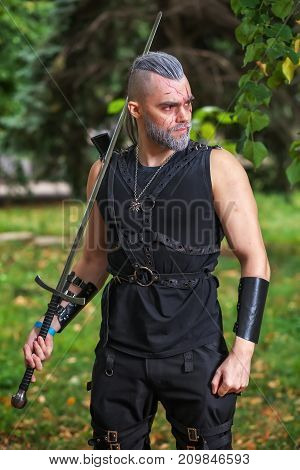 Cosplay character dressed like a Geralt of Rivia from the game The Witcher. Strong warrior with a sword in his hands. poster