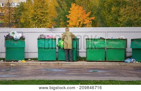Poor homeless old man searching in garbage in autumn time. Men rummaging in trash container looking for food and reusable goods