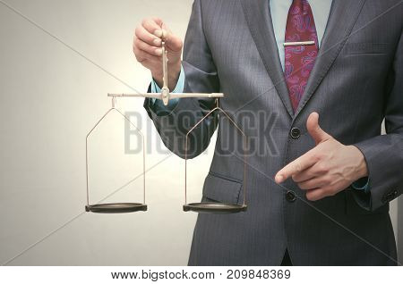 Business man holds in his hands a scales with empty bowls with copy space. Risk assessment. Judge holding empty scales.