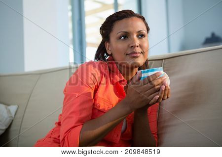 Thoughtful woman having coffee in the living room
