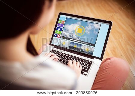 Composite image of various video and computer icons against asian woman using laptop with copy space