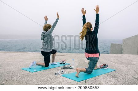 Back view of two unrecognizable women stretching outdoors by sea pier