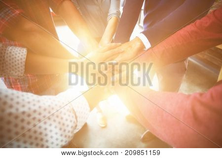 Team of businesspeople forming hand stack in office