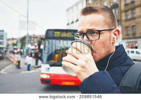 Morning coffee on the city street. Young man drinking hot coffee from the disposable cup and listening music in earphones.