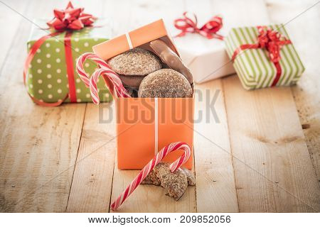Gift box loaded with gingerbread - Orange colored gift box full of sweets gingerbread and candies on a wooden table