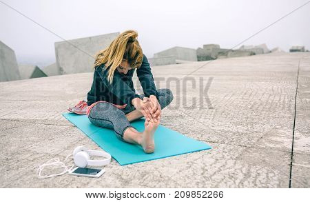 Young woman stretching legs on mat by sea pier