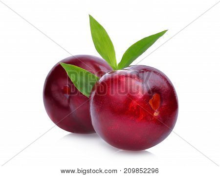 two whole of cherry red plum with green leaves isolated on white background
