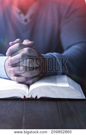Mid section of man with bible praying at wooden desk