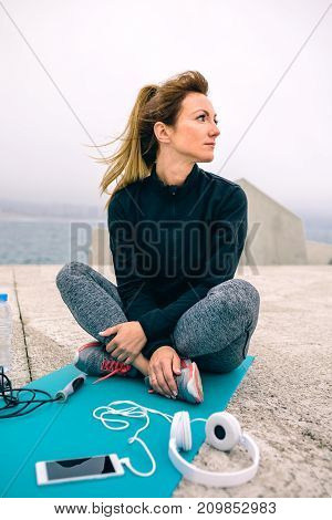 Young woman sitting on yoga mat with sport accessories outdoors