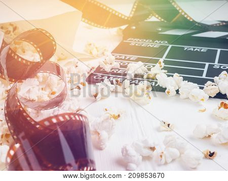 Clapperboard, A Roll Of Film, And Popcorn On The Table