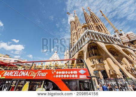 BARCELONA, SPAIN - August 16, 2017: Tourist bus near the famous Sagrada Familia roman catholic church in Barcelona, designed by catalan architect Antoni Gaudi