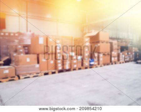 Warehouse industrial and logistics companies. blurry lots of boxes Commercial warehouse. Boxes and crates stocked on the shelves of three storey. The effect of motion blur. Bright sunlight.