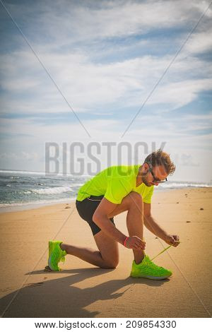 Tying jogging / running shoes on a tropical sandy beach near sea / ocean.
