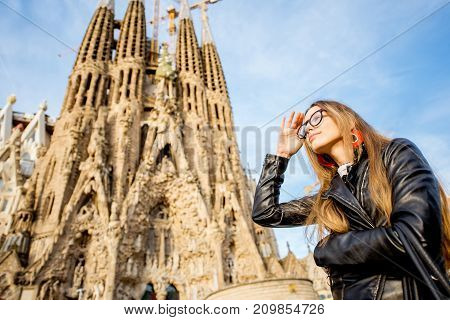 BARCELONA, SPAIN - August 17, 2017: Young woman in front of the famous Sagrada Familia roman catholic church in Barcelona, designed by catalan architect Antoni Gaudi