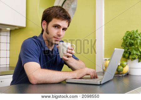Young Man With Warm Drink At Computer