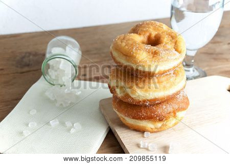 donuts glazed with a sugar icing on a rustic wooden table
