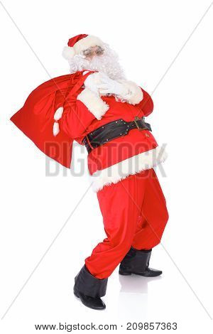 Santa Claus carrying big bag. Isolated on white background. Full length portrait.
