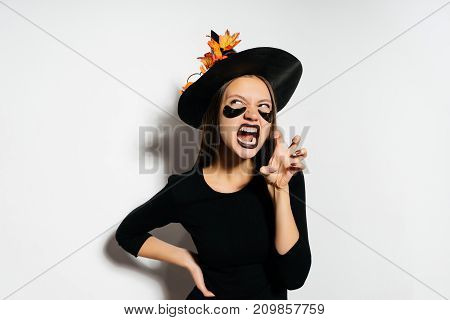 young sexy gothic girl in the image of a witch in halloween, in a big black hat depicts a tiger