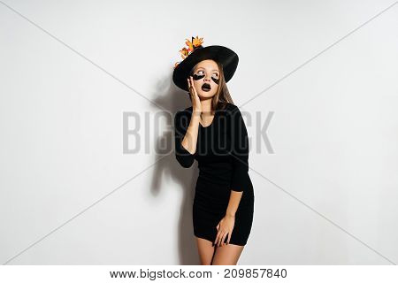 young sexy gothic girl in the image of a witch in halloween, in a big black hat dreamily looks up