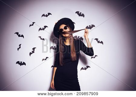 young sexy gothic girl in the image of a witch in halloween, in a big black hat, decorated with yellow leaves playing with her hair