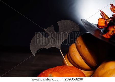 a composition for decorating a house for halloween, lie yellow and orange gourds, a big black witch hat decorated with autumn yellow leaves