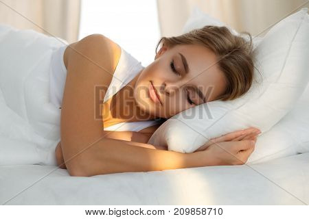 Beautiful young woman sleeping while lying in bed comfortably and blissfully Sunbeam dawn  on her face.