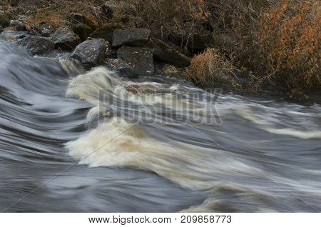 Rapid river flow and boulders with fallen leaves on the shore in autumn