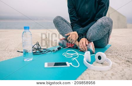 Low section of woman sitting on yoga mat with sport accessories