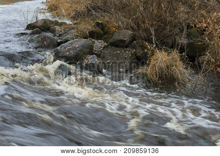 Autumn turbulent river flow and boulders with fallen leaves on the river bank