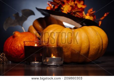 a composition for decorating a house for halloween, lie yellow and orange gourds, a big black witch hat decorated with autumn yellow leaves and candles burning
