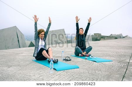 Senior woman stretching arms with female coach by sea pier