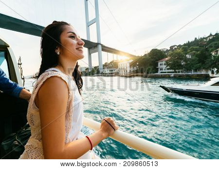 Young freedom happy girl is traveling by boat under a modern bridge at sunset