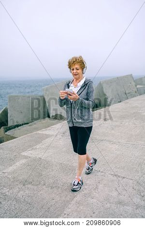 Senior sportswoman with headphones walking and looking at her smartphone