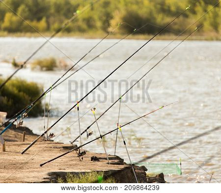 fishing rods on the river bank in nature .