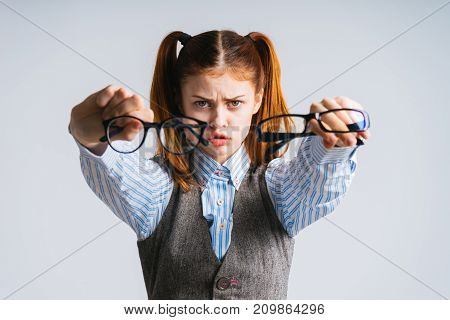 A serious girl with two tails holds in her hands two pairs of glasses. glasses close-up, isolated