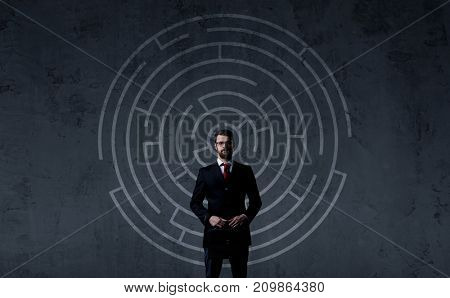 Businessman with briefcase standing over labyrinth background. Business, strategy, concept.