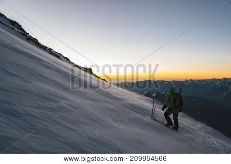 the mountaineer professionally equipped at dawn of the sun walks on the slope in the early morning and the snow drifts over the snow above the snow. The concept of travel and conquest of steep peaks