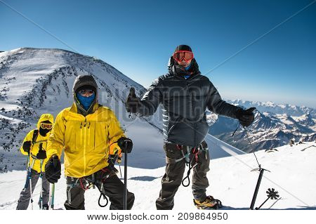 A middle-aged climber in a down jacket and harness shows a thumb up next to his friends on the way to the top of a snow-capped mountain. The concept of rest and climbing high mountains with friends