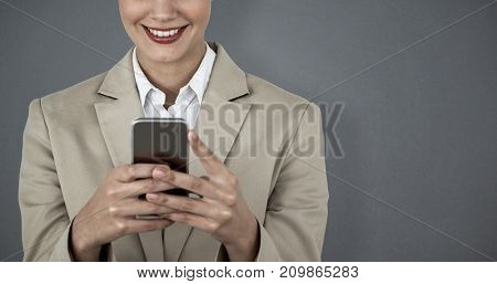 Close up of smiling businesswoman using mobile phone against grey background