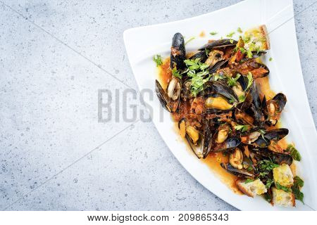 Traditional Italian blue mussel in white wine sauce as close up on a plate with copy space left