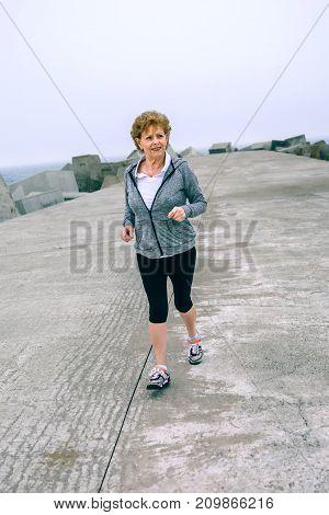 Senior sportswoman walking by sea concrete pier