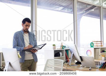 Male executive writing in diary at his desk in office